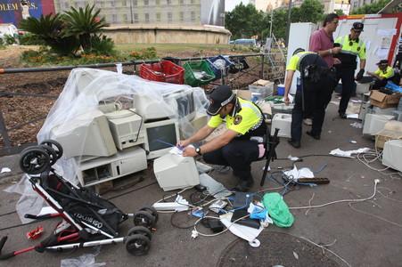 Trabajadores de la brigada de limpieza municipal retiran ordenadores de la acampada de la plaza de Catalunya, este viernes.