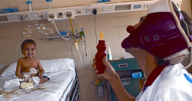 Soleimán Sumar, en diálisis peritoneal, miraembelesado las pompas que fabrica el Dr. Anestesio, del colectivo Pallapupas, en el Hospital Sant Joan de Déu. TINO SORIANO