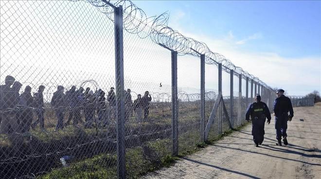 Policías húngaros vigilan a refugiados tras una valla temporal en la frontera con Serbia, cerca de Morahalom, el 22 de febrero del 2016.