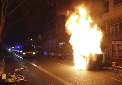 Un contenedor quema durante los altercados por el desalojo de La Carbonería.