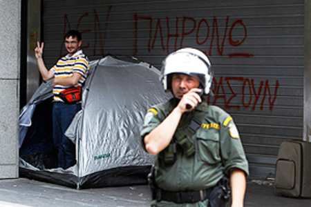 Un hombre en paro acampa frente al Ministerio de Finanzas en Atenas mientras analistas del FMI y la UE realizan una visita este miércoles