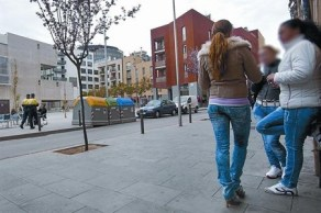 Unes dones a l'Illa Robador, mentre dos guàrdies urbans passen davant la nova Filmoteca, dimarts.