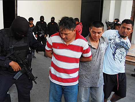 Un agente de la policía escolta a los últimos detenidos en el caso. |Efe