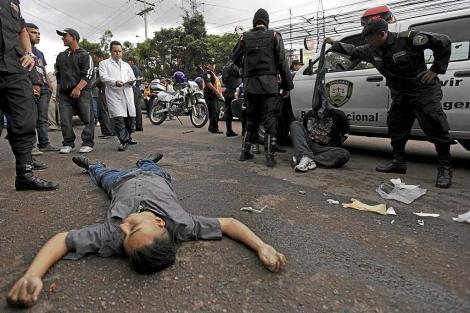 El cadáver de un hombre ligado al crimen organizado en una calle de Tegucigalpa. | Reuters