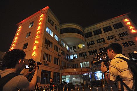 Dos periodistas chinos graban el hospital de Sichuan donde está aislado el primer caso de gripe porcina en el país. | AP