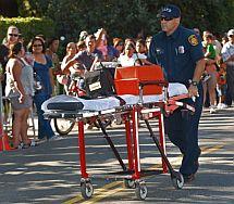 Un sanitario traslada a un joven que se desmayó ante la casa de Jackson. | AP