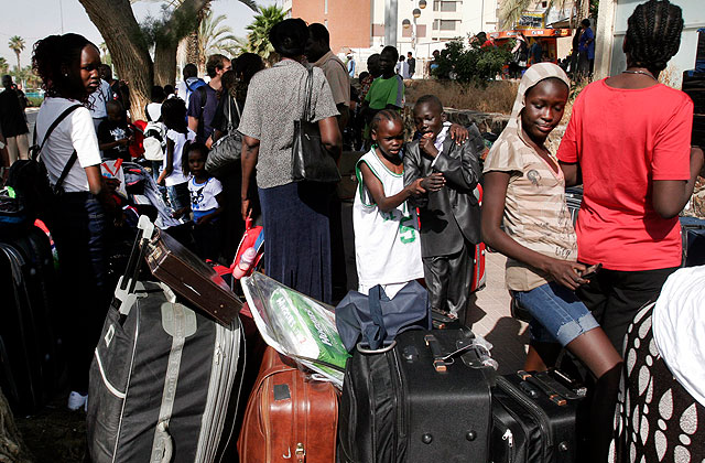 Un grupo de sursudaneses espera en Tel Aviv el autobús que les llevará al aeropuerto. | AFP