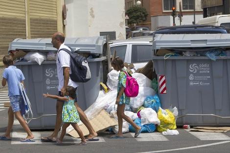 Una familia pasa delante de dos contenedores de basura repletos. | C. Zambrano