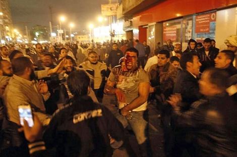Un opositor a Mursi, herido, rodeador de partidarios del presidente. / FOTO: Afp