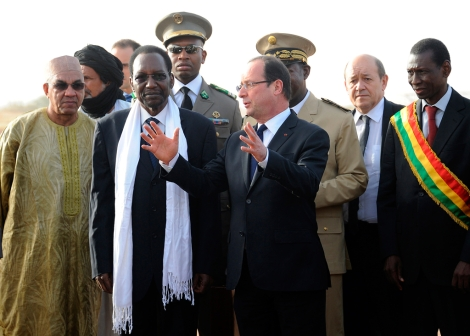 El presidente francés Hollande intercambia palabras con el presidente interino de Mali, Dioncounda Traoré, entre el séquito que le esperaba en el aeropuerto a su llegada a Mali. | Afp