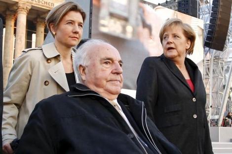 Kohl, en silla de ruedas, llevado por su mujer y acompañado por Merkel.   E.M.