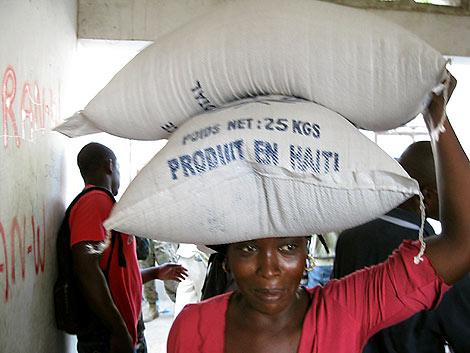Una mujer en Haiti transporta un saco de comida.   AFP