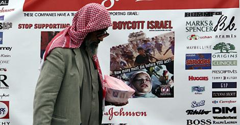 Bahrein, un hombre frente a un cartel que llama al boicot a empresas israelies
