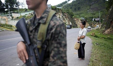 Una mujer espera el autobús junto a un control militar en las afueras de Tegucigalpa. | Reuters