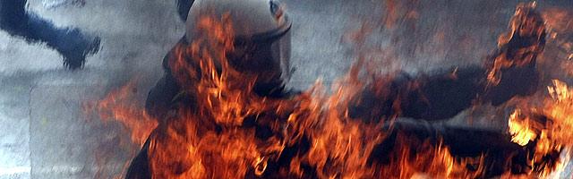 Policía ardiendo por un coctel molotov en Grecia
