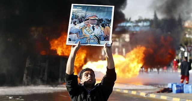 Partidarios de Gadafi sostienen un retrato suyo en Trípoli. | Reuters