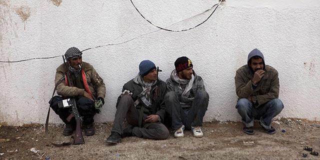 Rebeldes libios esperan sentados en un punto de la ciudad de Ajdabiyah. | Reuters