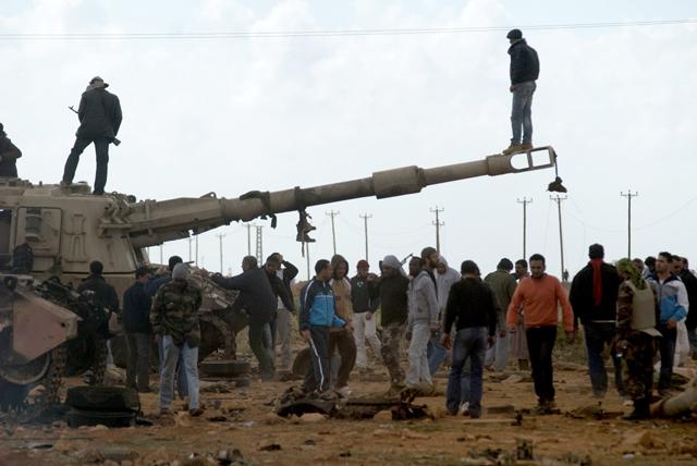 Un grupo de insurgentes junto a carros de combate del Ejército. | Efe