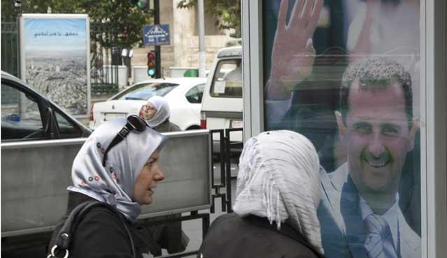 Dos mujeres frente a un cartel de Bashar Asad en Damasco, Siria. | Ap