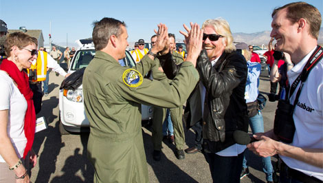 Richard Branson (con gafas de sol) saluda a uno de los pilotos tras el aterrizaje. | V. Galactic.