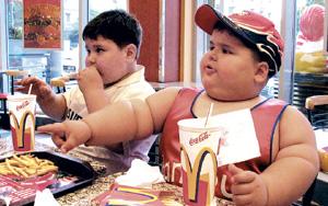Dos niños obesos comiendo en un restaurante de comida rápida. (Foto: El Mundo)