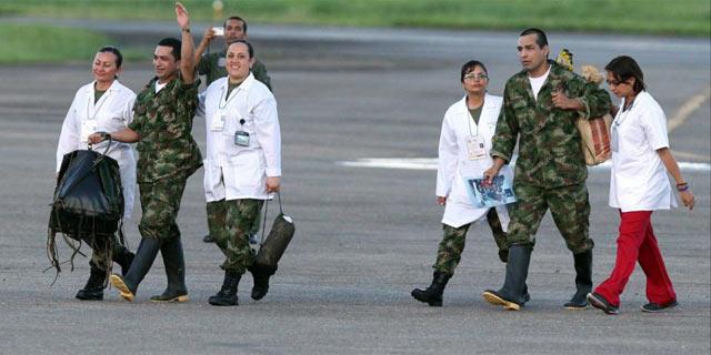 Dos de los rehenes liberados este lunes junto con el equipo médico que los atiende. | Efe
