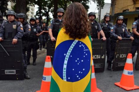 Una manifestante ante los agentes que ya custodian el estadio.| Afp