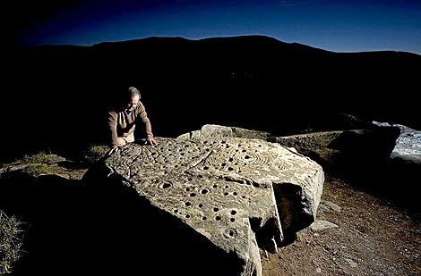 Juan Carlos Campos posa junto a una de las piedras con petroglifos. (Foto: Amando Casado)