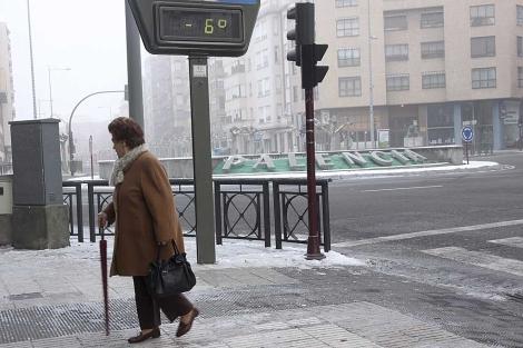 Una mujer pasa delante de un termómetro en Palencia que marca 6 grados bajo cero.   Efe