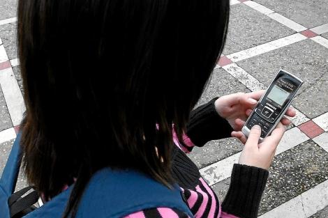 Una joven envía un SMS.