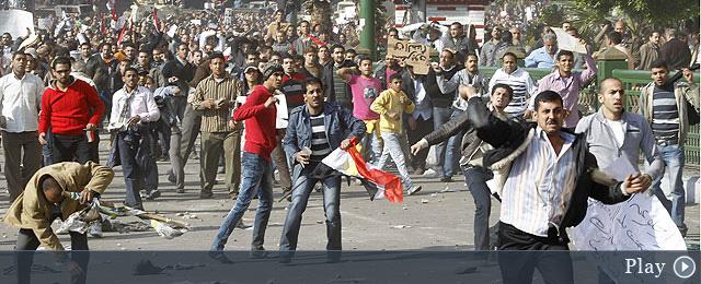 Ciudadanos egipcios levantan sus zapatos como muestra de desprecio a Mubarak en la Plaza de Tahrir. | Efe | MÁS IMÁGENES