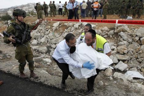 Los servicios de emergencias retiran el cuerpo de Palmer en Hebrón. | Reuters
