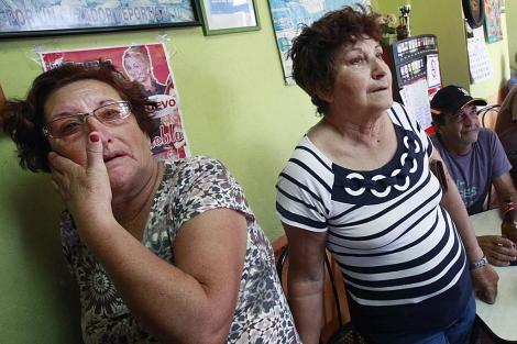 Dos vecinas de El Hierro siguen las noticias a través de la televisión. | Afp/Desiree Martín