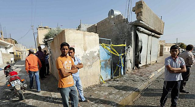 Varios vecinos del pueblo de Akcakle, en el edificio bombardeado, donde murieron cinco civiles. | Reuters