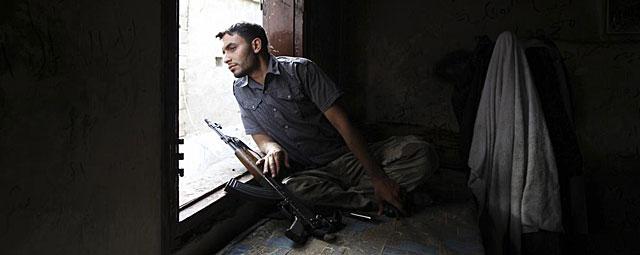 Un rebelde del Ejército Libre Sirio descansa durante su guardia en Alepo. | Reuters