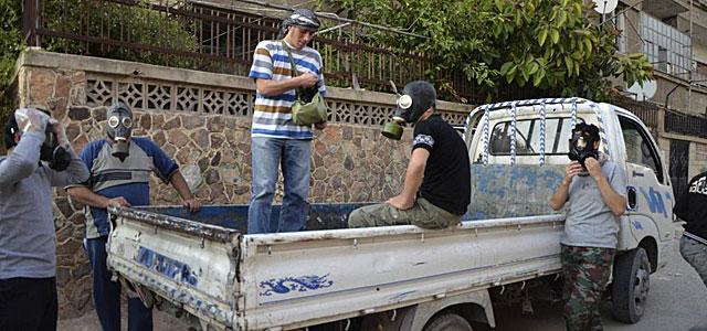 Activistas sirios con máscaras siguen buscando cadáveres. | Reuters