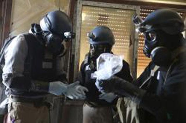 Inspectores de la ONU con cámaras antigás recogiendo muestras en Siria . | Reuters