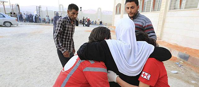 Trabajadores de la Cruz Roja ayudan a una mujer cerca de Damasco. | Efe