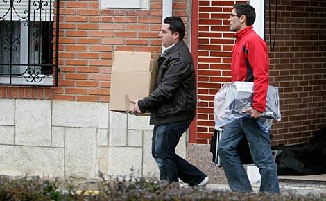 Dos policías cargan con pruebas tras registrar la vivienda de Marta Domínguez. (Foto: Reuters)