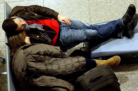Dos pasajeros duermen en Barajas a la espera de su vuelo. | Efe