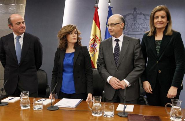 De izquierda de derecha, el ministro de Economía, Luis de Guindos, la portavoz Soraya Sáenz de Santamaría, el titular de Hacienda, Cristóbal Montoro, y la ministra de Trabajo, Fátima Báñez, tras la rueda de prensa.   Efe
