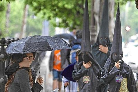 Nazarenos de la Hermandad de los Estudiantes, en Sevilla, bajo la lluvia en 2011. | Efe