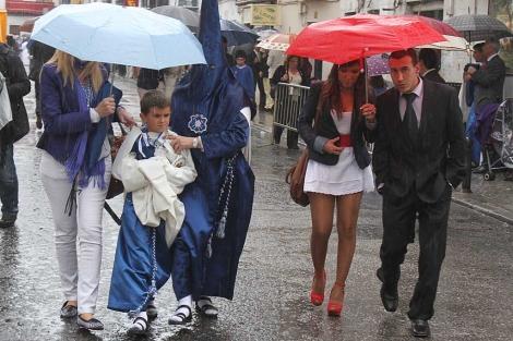 Nazarenos de la Hiniesta de vuelta a casa tras suspenderse la procesión. | Carlos Márquez