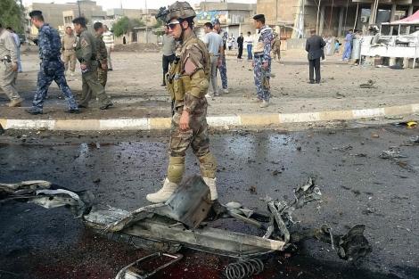 Un soldado iraquí, entre los restos de un coche bomba en Kirkuk. | Afp