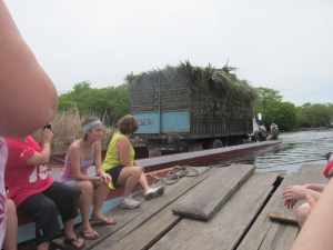Riding on the ferry and passing another ferry with a sugar cane truck