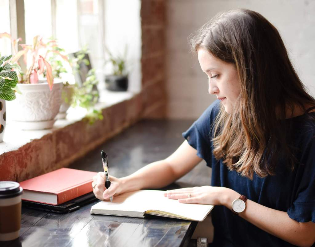 Woman writing at a table | 5 STEPS TO CREATING NEW HABITS