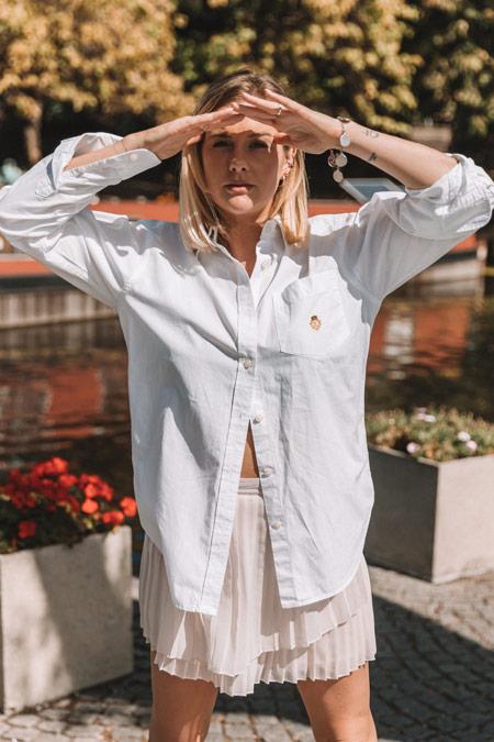 Estilo e autoconfiança: Eliza veste camisa branca larga e saia plissada. Ela faz uma pose forte, cobrindo os olhos do sol.
