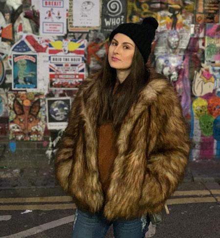 na foto Betina, uma das sócias da Pleasure is Power, veste um casaco de pele e um gorro preto, é branca, de cabelos castanhos. Está em pé em frente a uma parede grafitada.