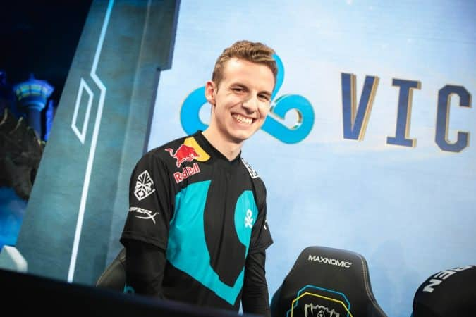 """C9 LoL top laner Eric """"Licorice"""" Ritchie stands up with a big grin in front of a monitor showing a C9 logo and the word victory"""