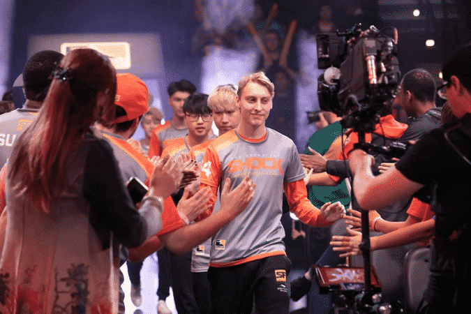 """Grant """"moth"""" Espe walks down an aisle in the Overwatch League arena with his fellow San Francisco Shock teammates and high fives fans"""
